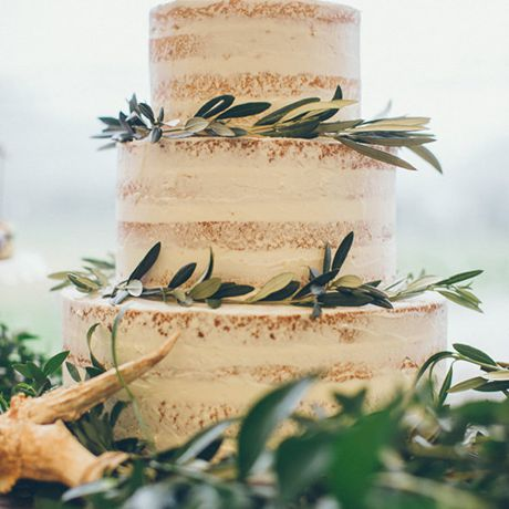 A three-tiered naked wedding cake trimmed with vines of eucalyptus