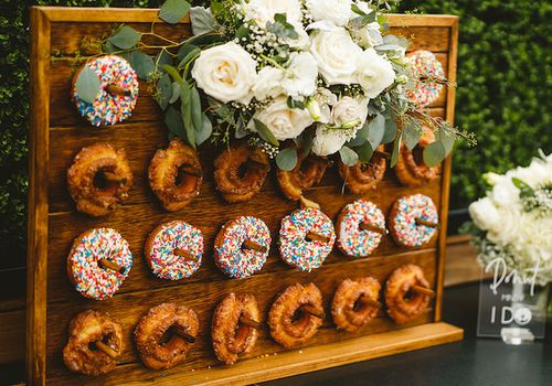 Small donut wall featuring white flowers for a small, intimate ceremony