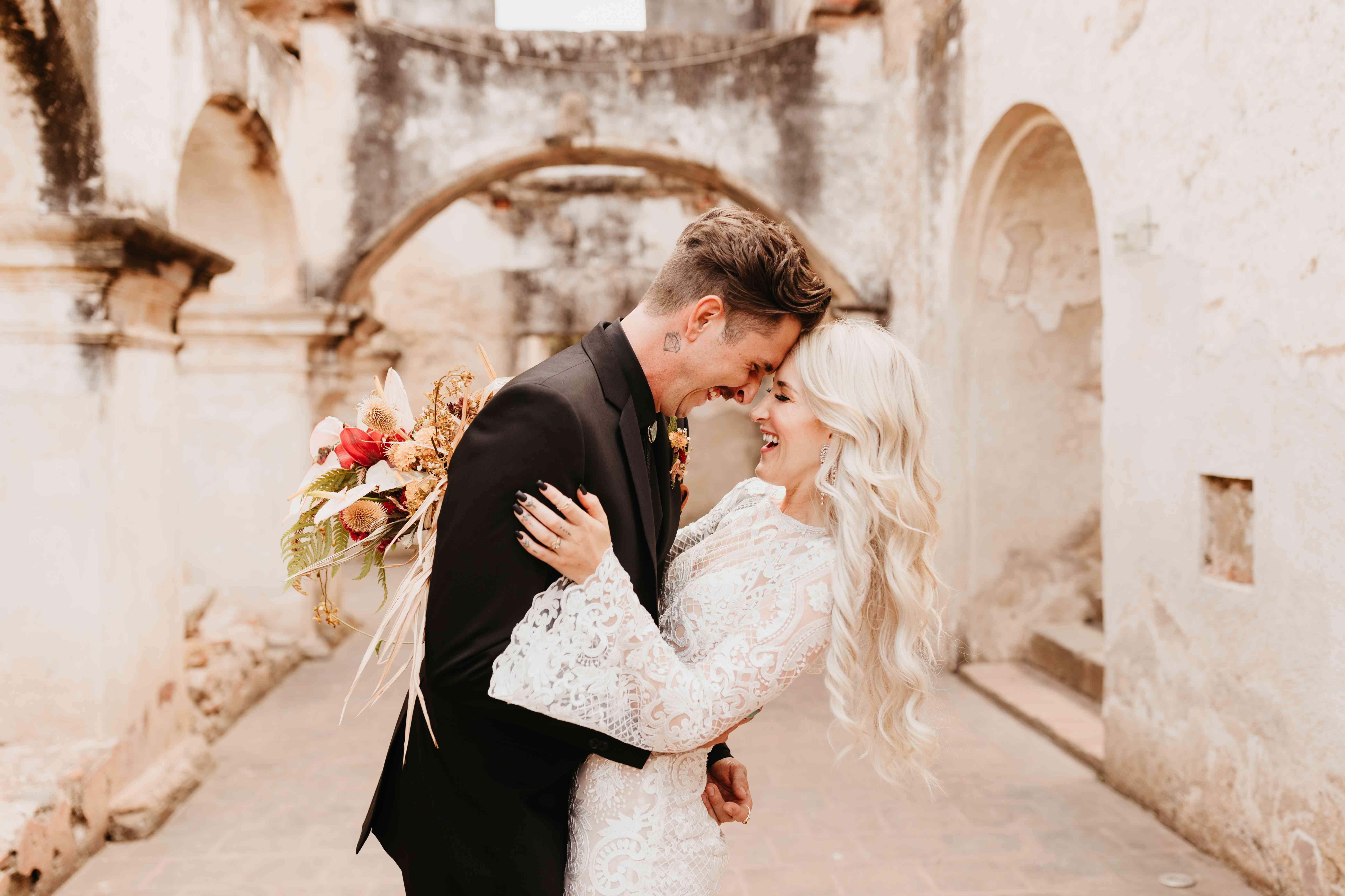 Bride and groom smiling and embracing, bride wearing black nail polish