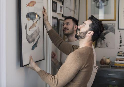 couple hanging art on wall