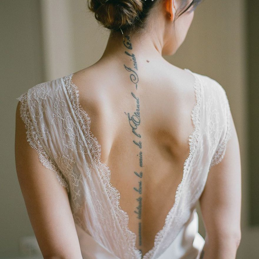 Bride with a spine tattoo wearing a low-back gown