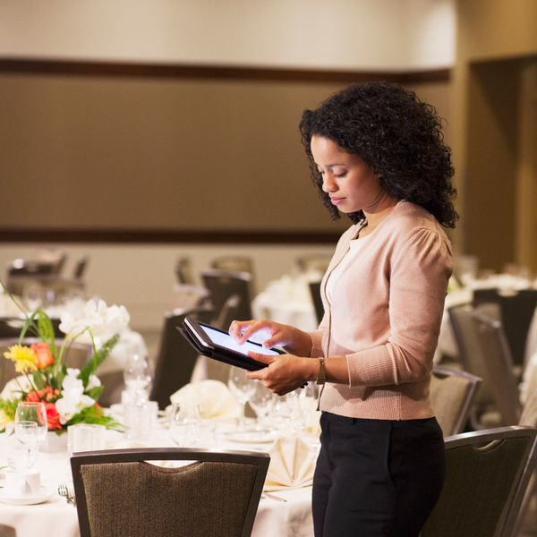 Wedding planner at a wedding reception venue looking on her iPad