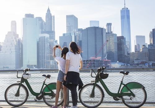 Couple takes selfie next to rental bikes and skyline in background
