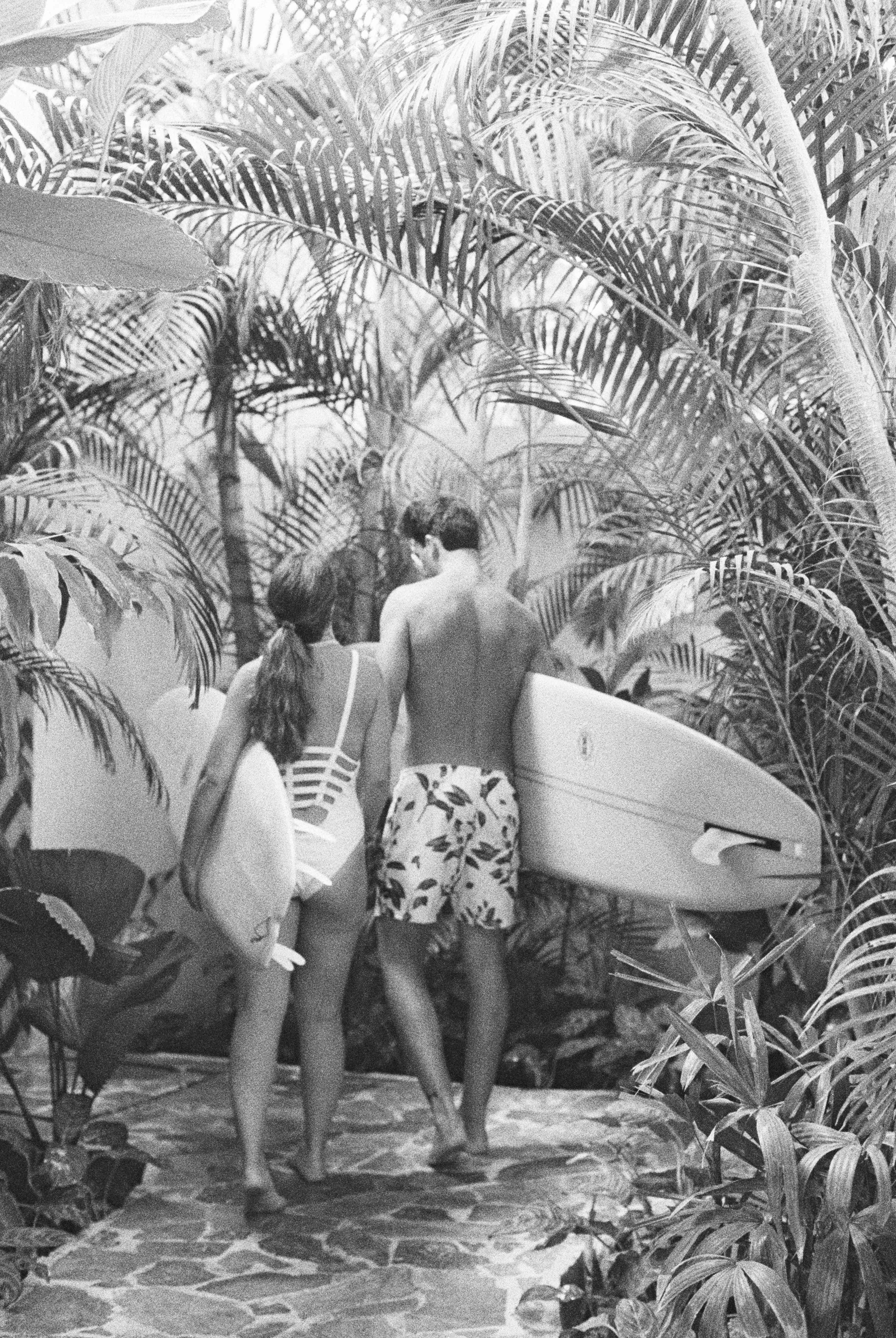 couple holding surfboards