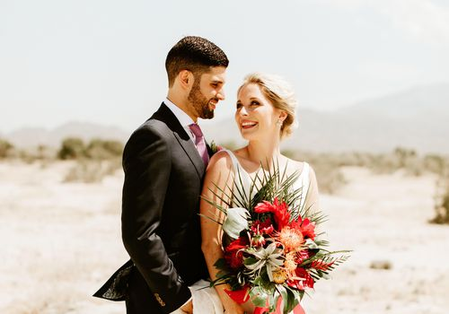 groom and bride with tropical bouquet in desert