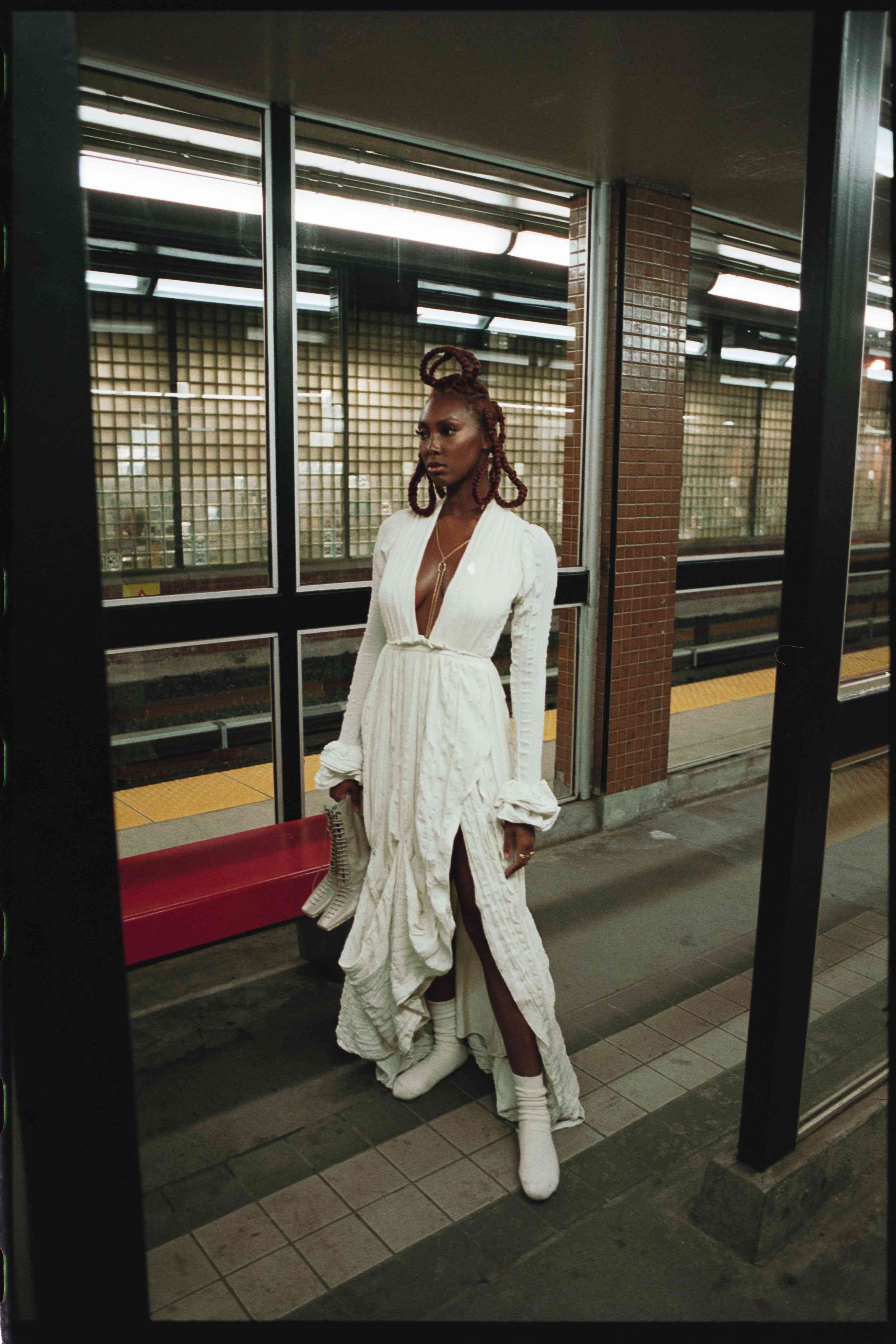 Woman standing in subway station wearing wedding gown.