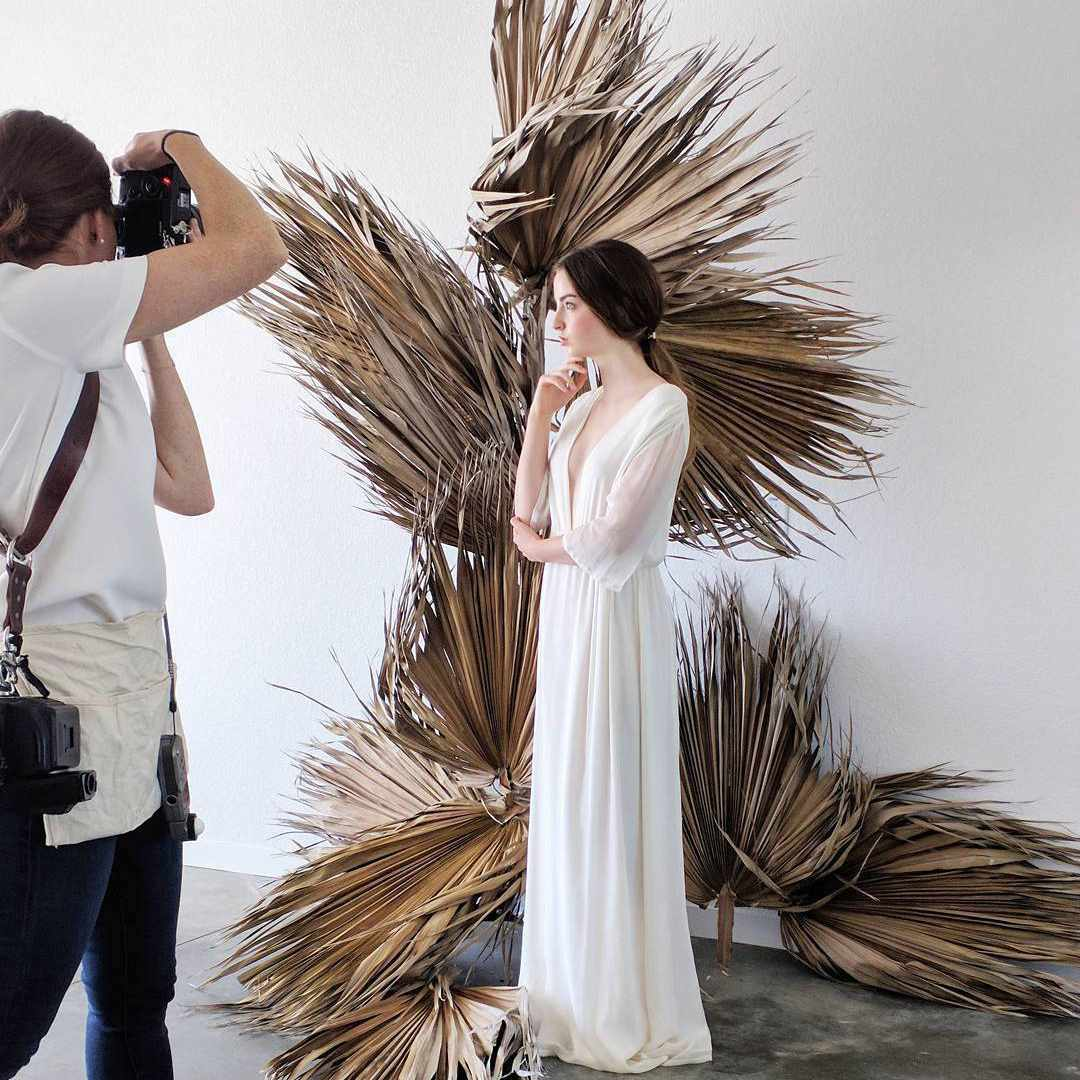 Ceremony backdrop of dried, oversized palm fronds