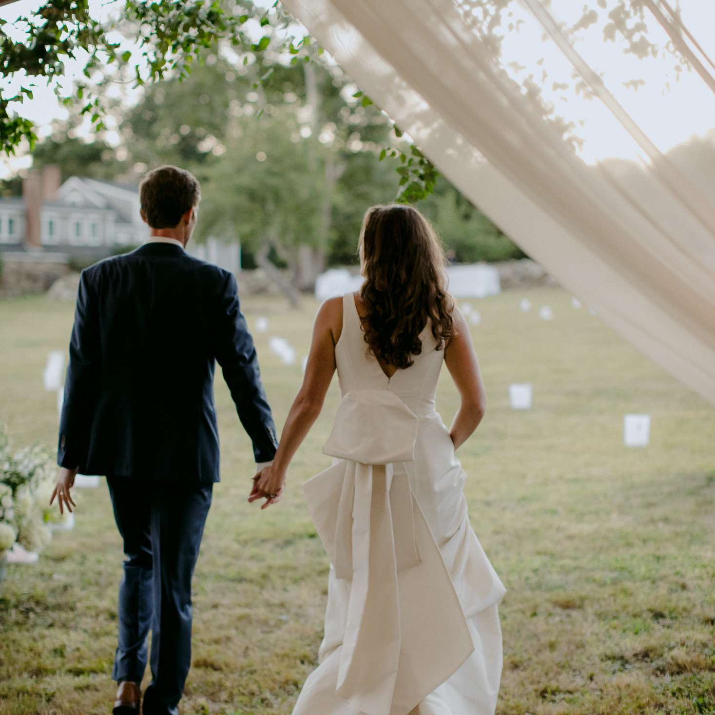 at-home rustic massachusetts wedding, bride and groom holding hands reception