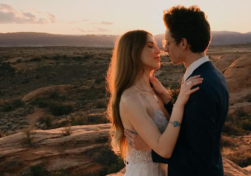 A couple posing for a video while getting eloped in the desert