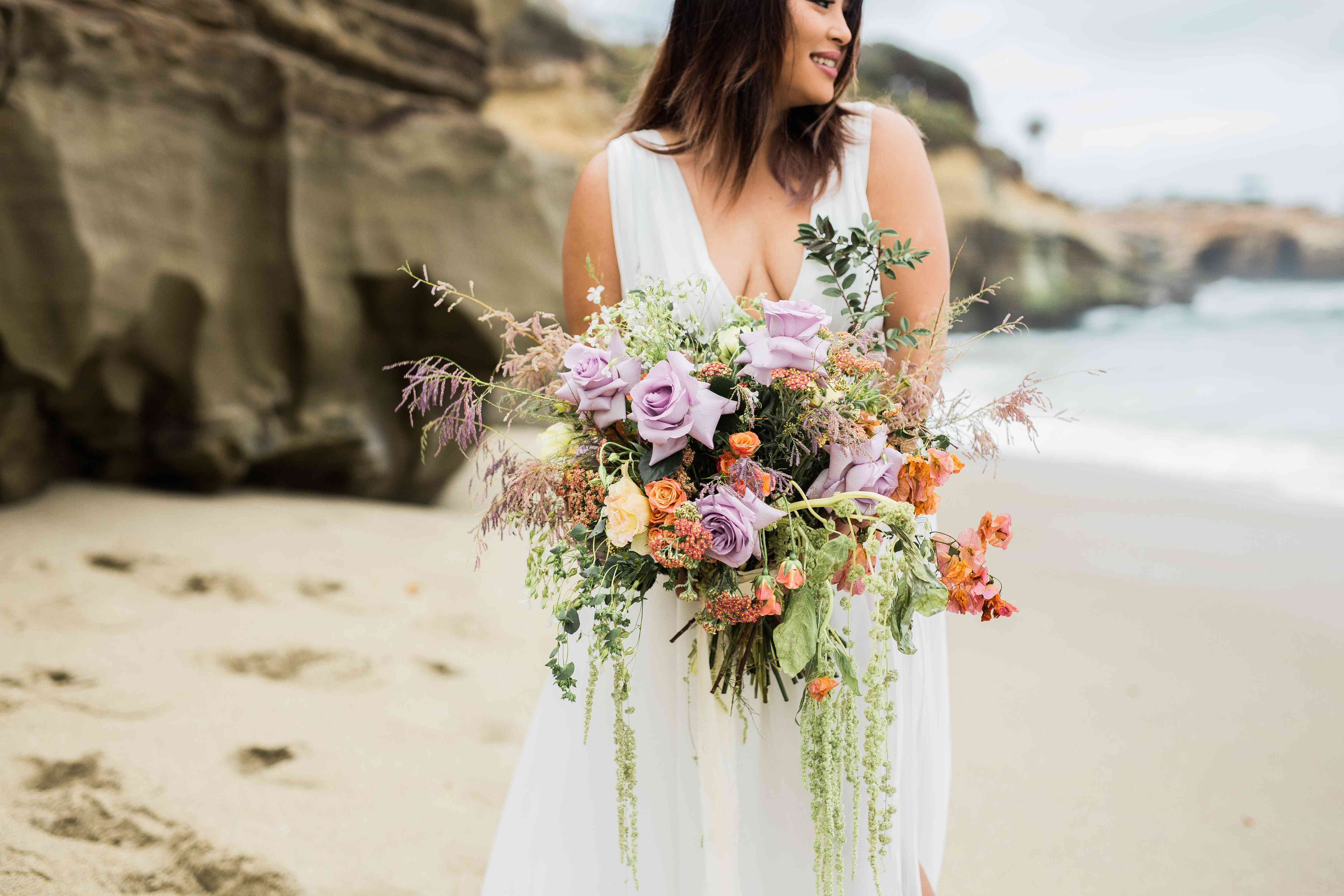 Bride holding a bouquet of purple and orange roses with trailing greens