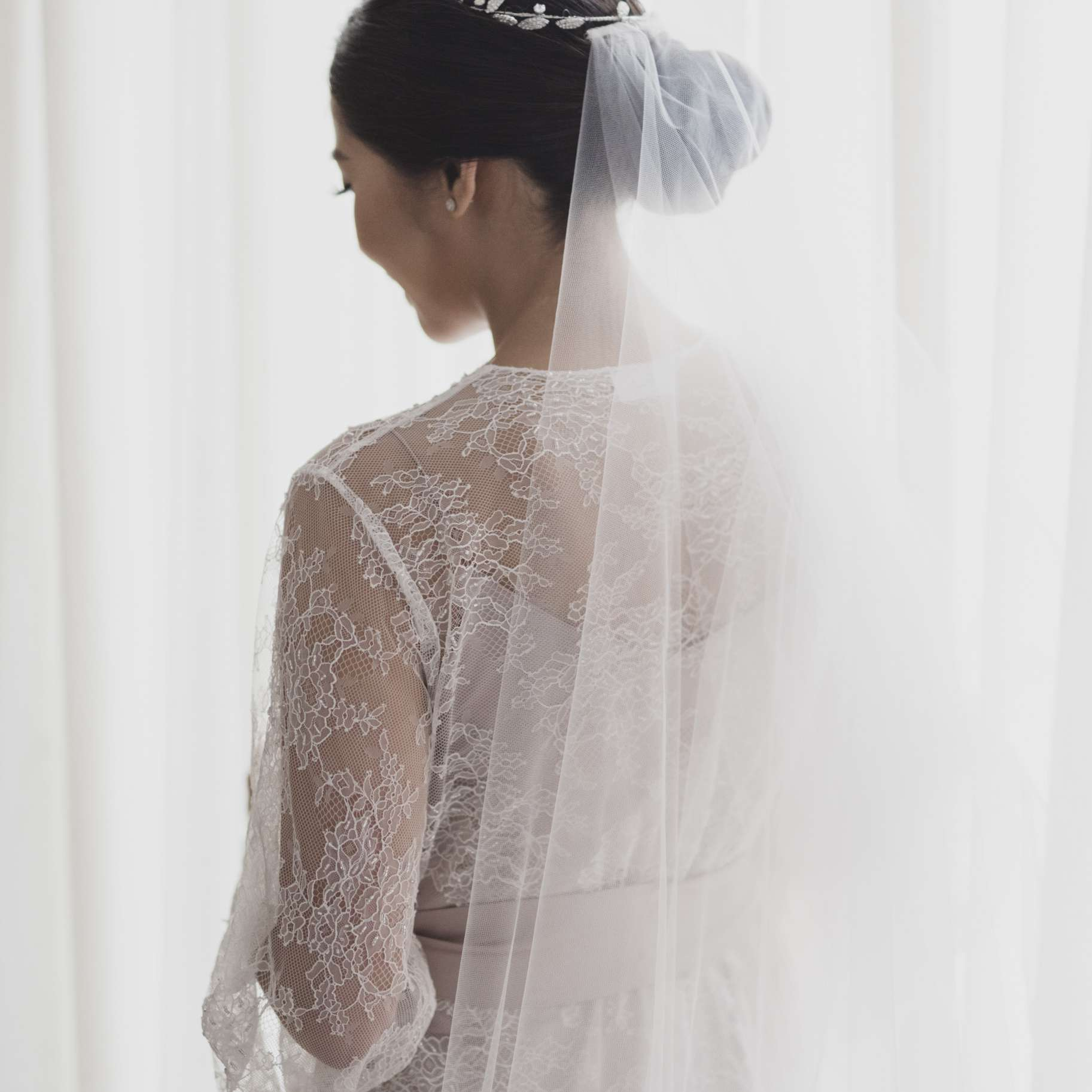 Bride in lace robe looking out window