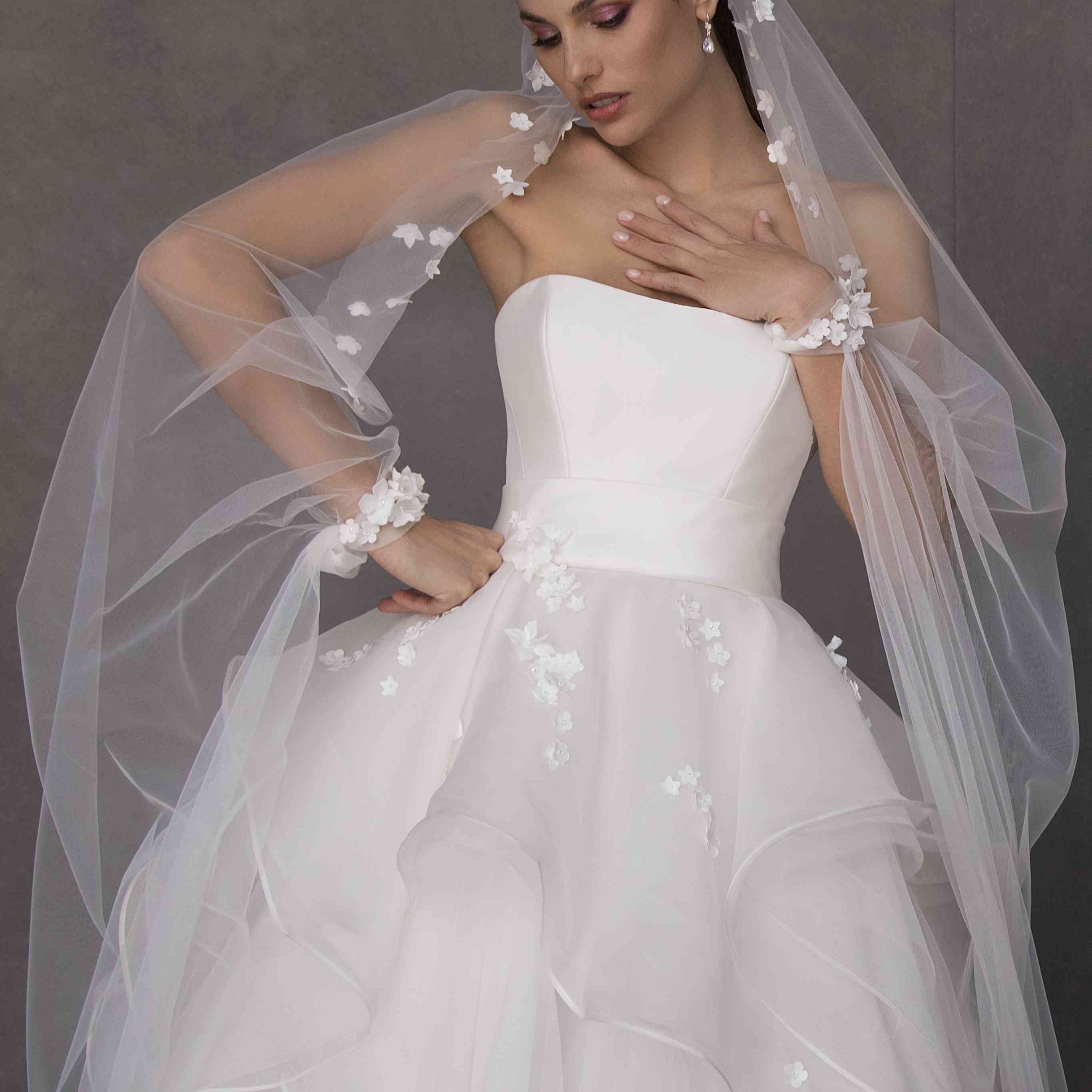 Model in strapless ballgown with a tiered tulle skirt with floral appliques
