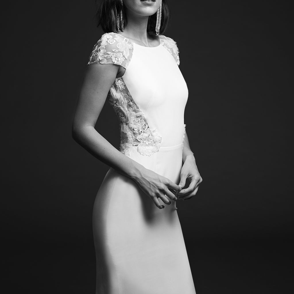 Model in short-sleeve crepe dress with 3D embroidery and cap sleeves