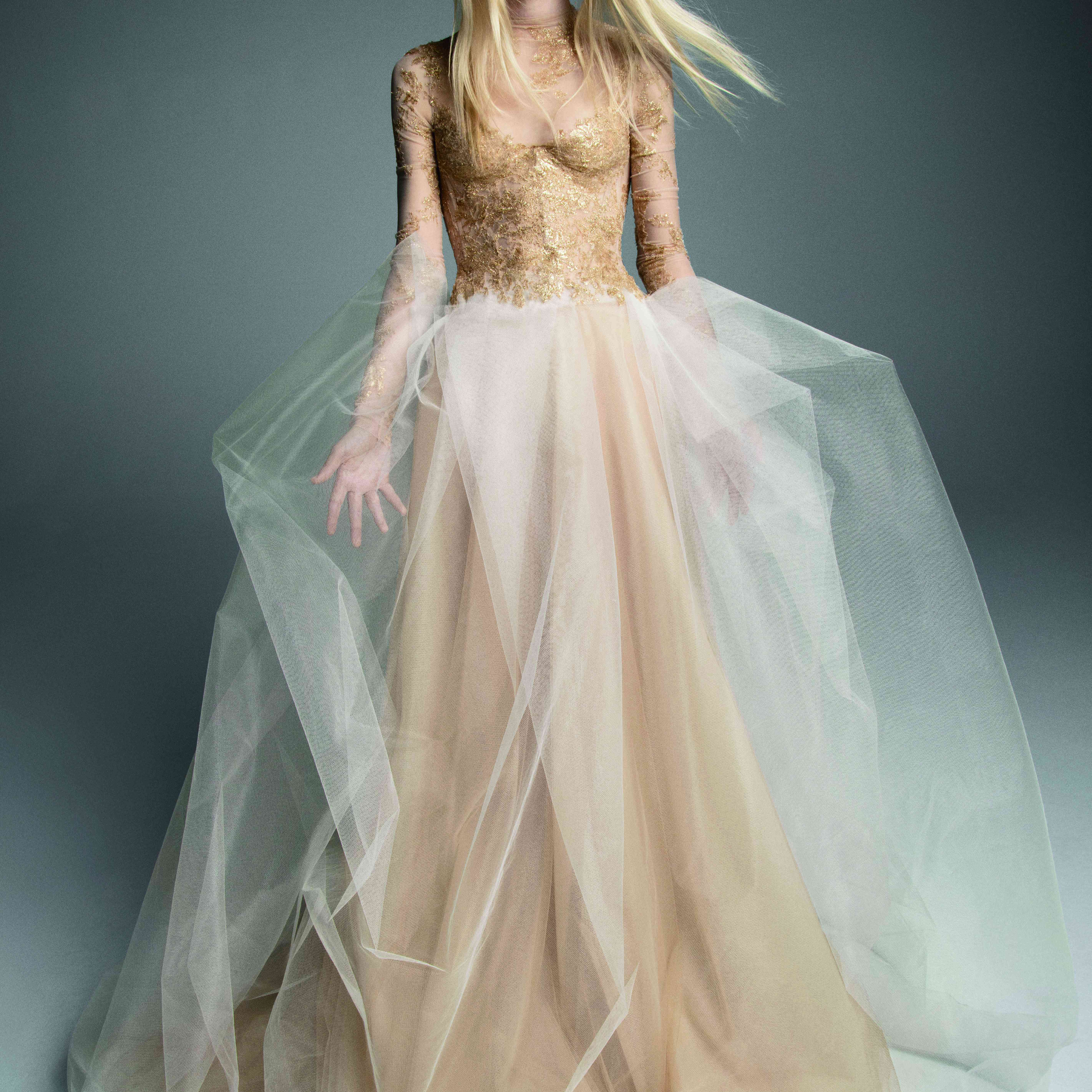 Model in long-sleeve nude gown with an embroidered bodice and a white tulle overskirt
