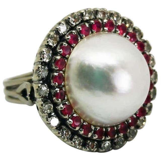 Pearl ring surrounded by 23 rubies and 25 diamonds.