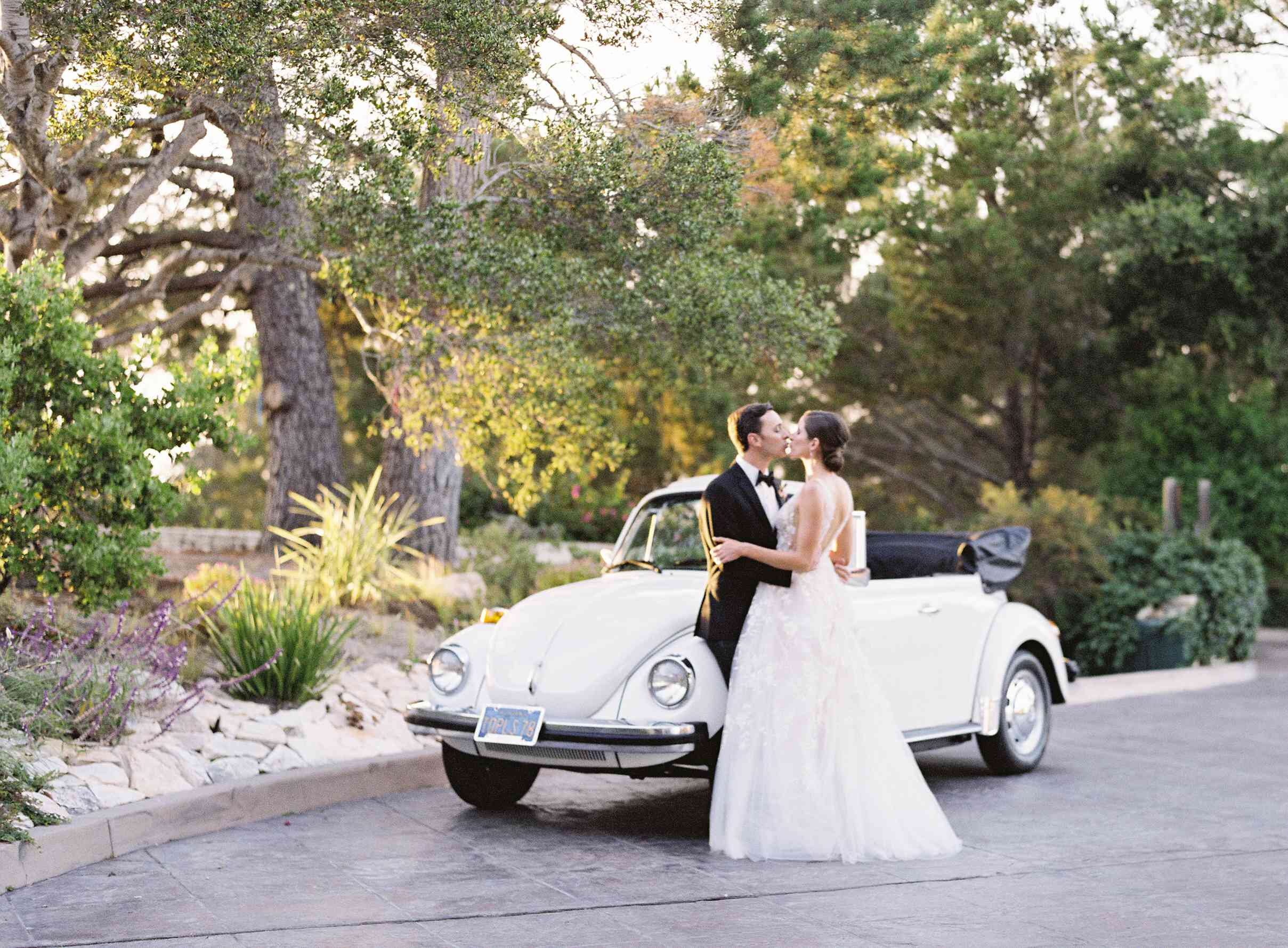 bride and groom with white convertible getaway car