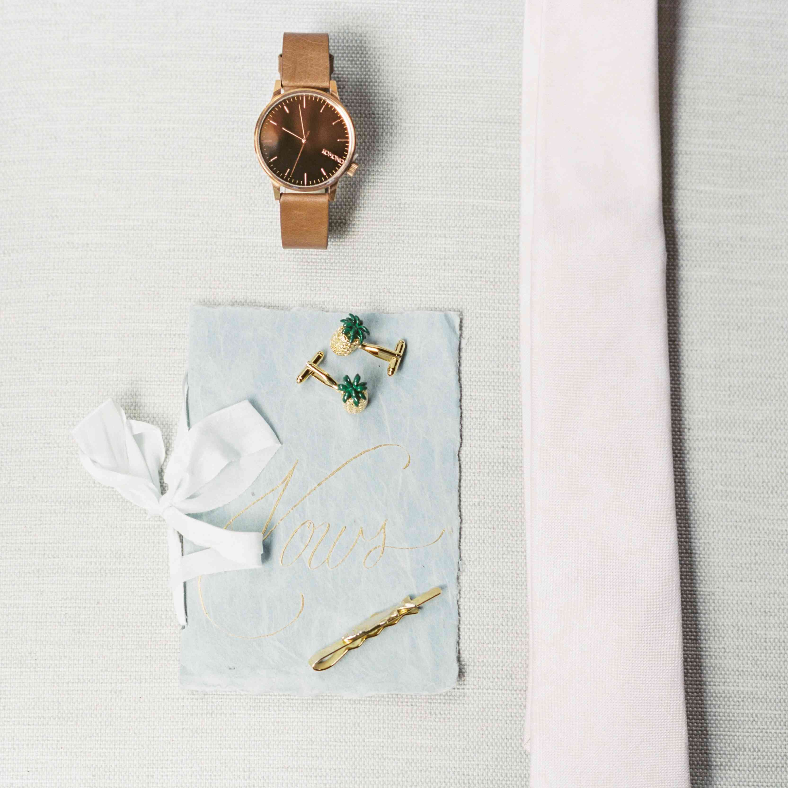Flat lay or watch, vow book, tie, and cuff links