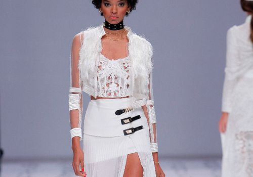 Model in a corseted top with crochet embroideries and 3D flowers and a crepe and pleated georgette skirt with a high slit and black and gold buckle details at the side, worn with a transparent bomber jacket with fringe