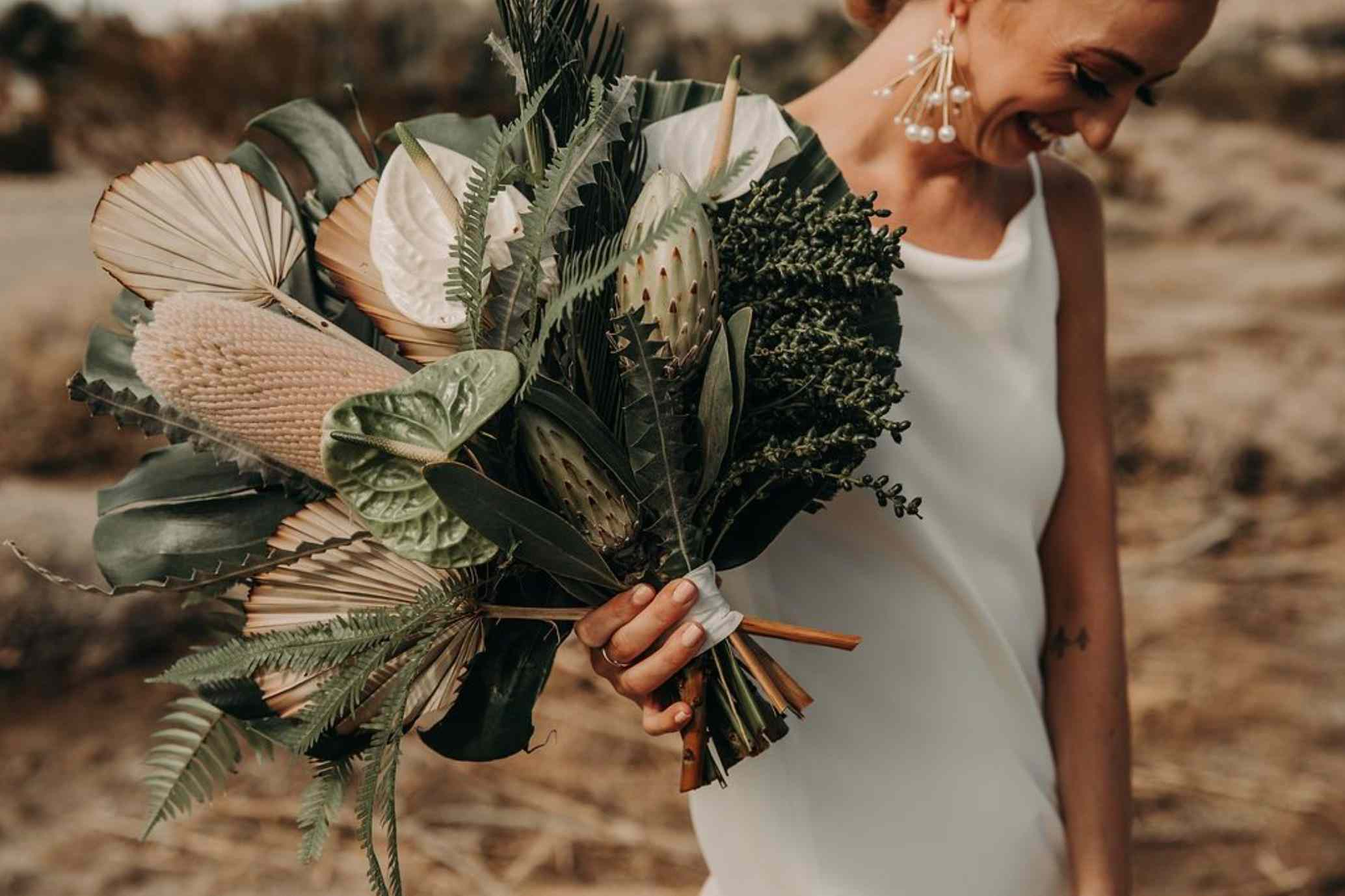 Tropical-inspired bouquet with giant monstera leaves, palms, and anthurium.