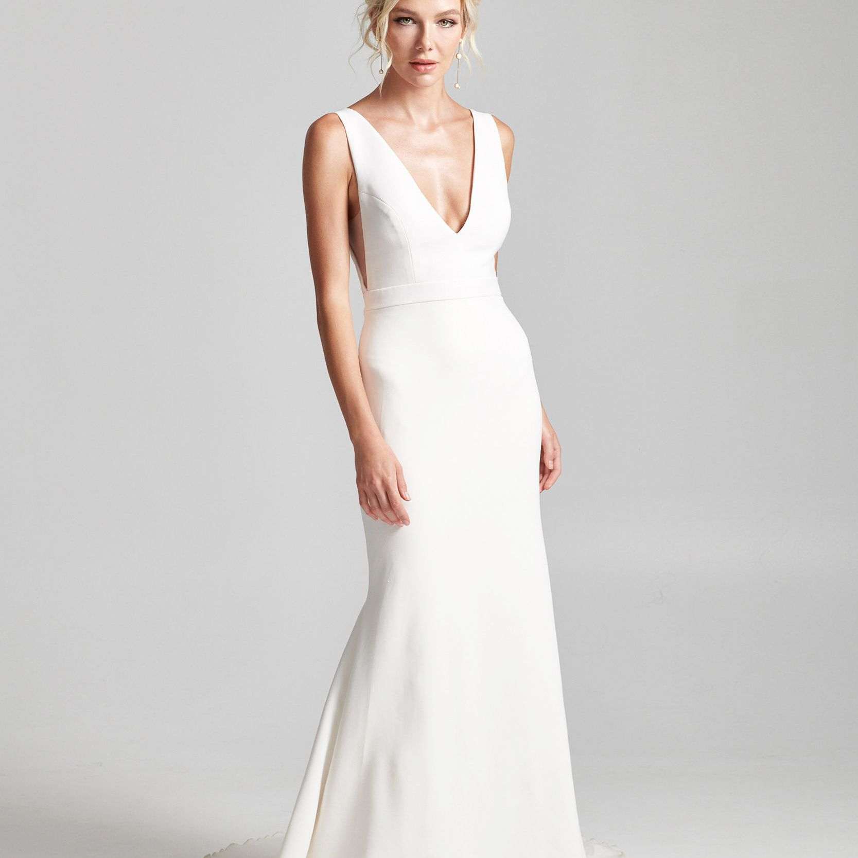 Model in sleeveless wedding dress with deep V neckline and banded waist