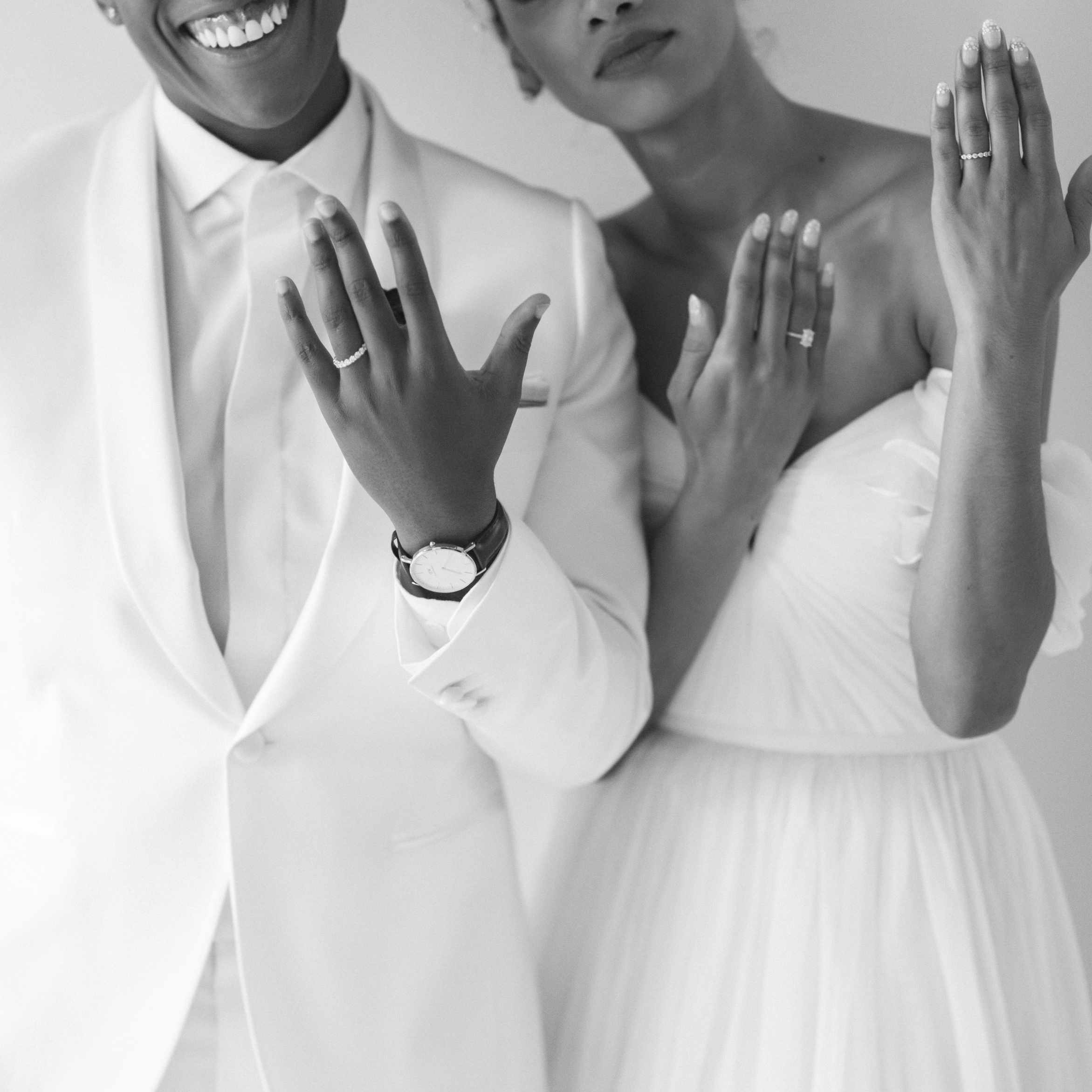 Newlywed couple holding up their hands to show off rings