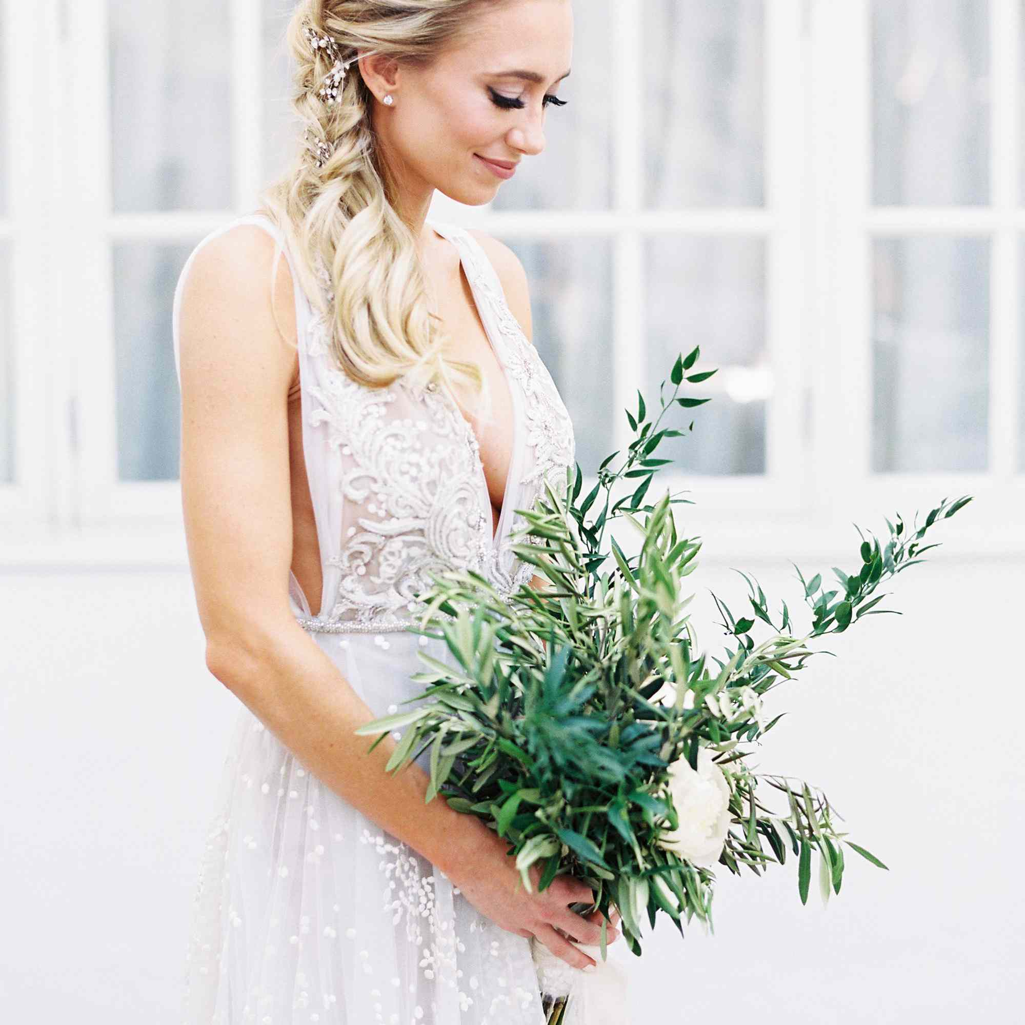 Bride holding bouquet of greenery