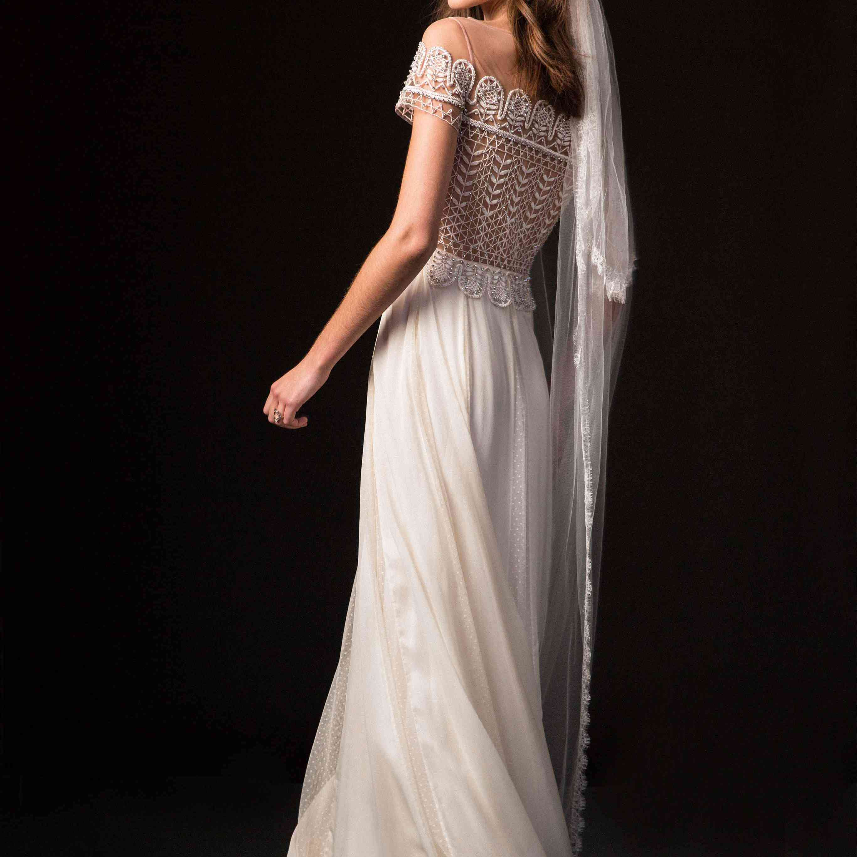 Model in illusion off-the-shoulder gown with an embroidered bodice and tulle skirt