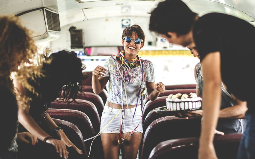 A young woman having a birthday party on a bus