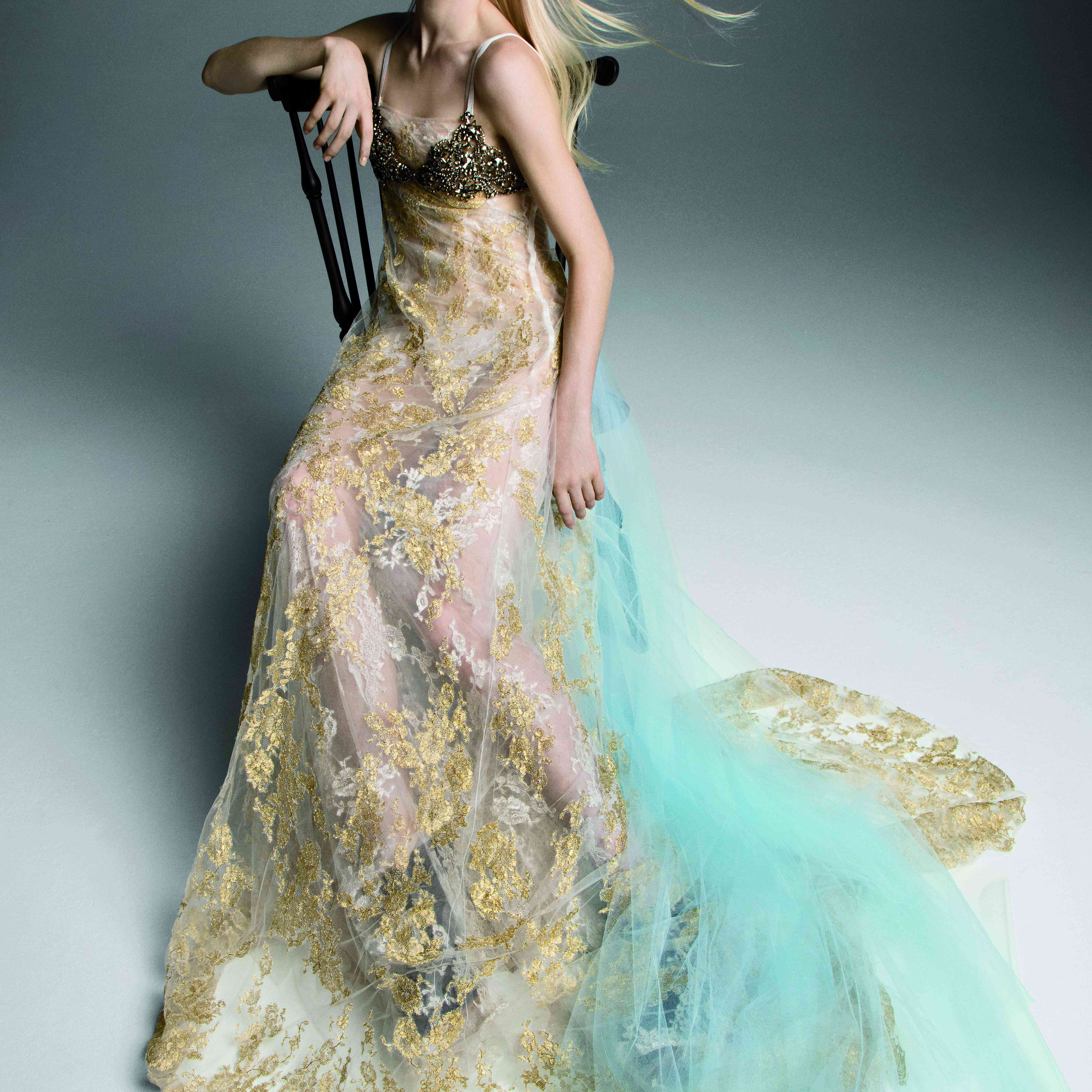 Model in spaghetti strap gown with gold and silver accents and a light blue train