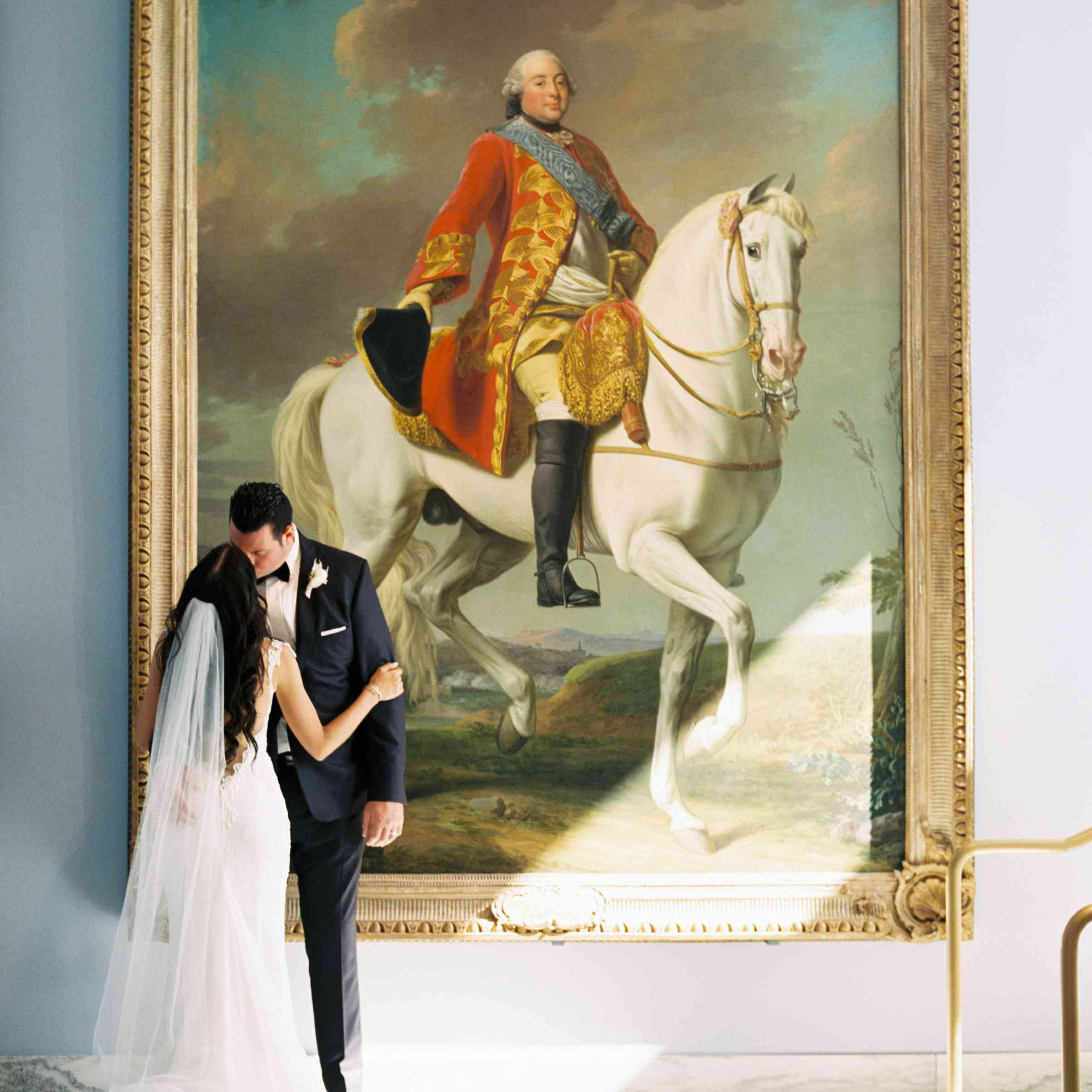 The bride and groom pose next to a painting