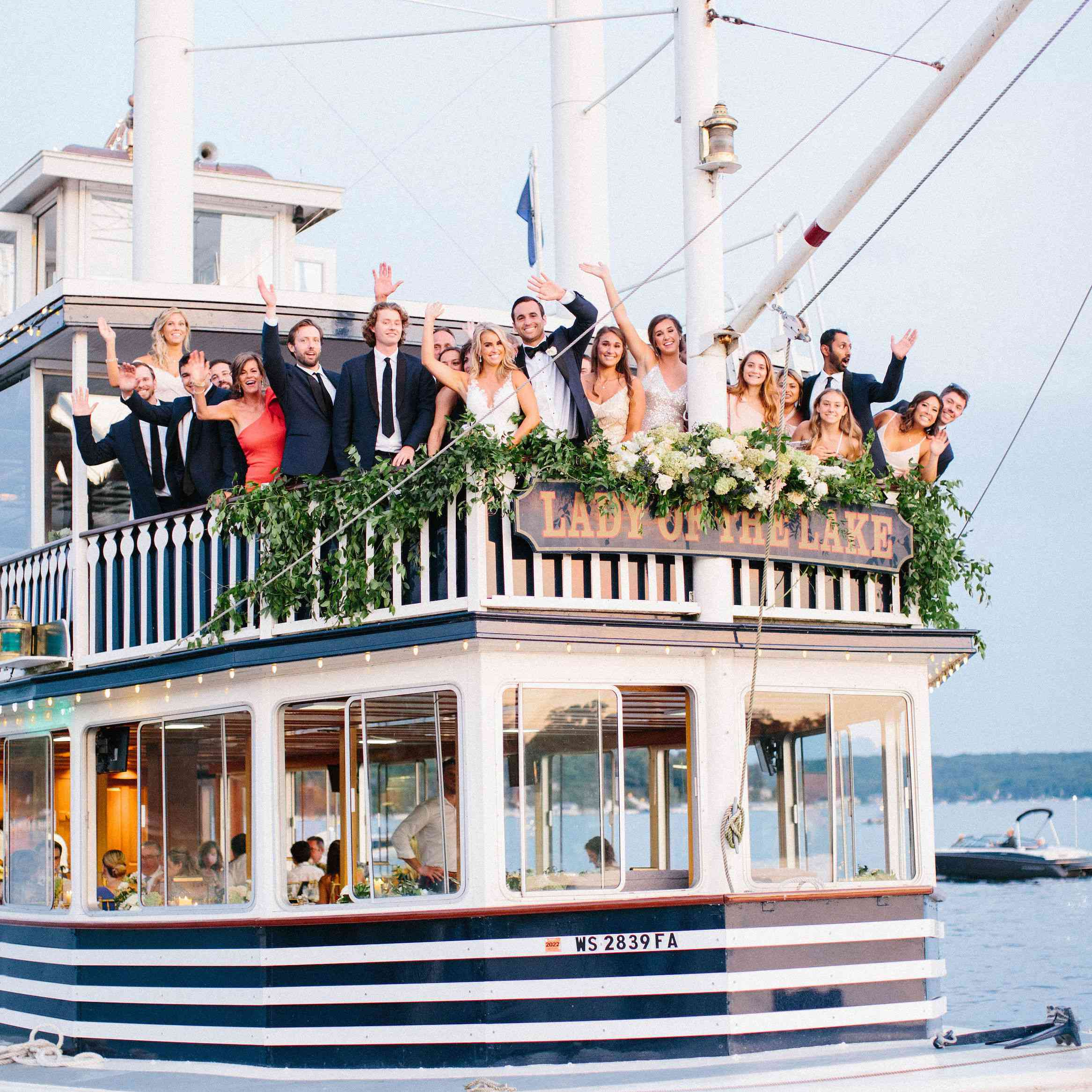 Wedding party waving from the deck of Lady of the Lake