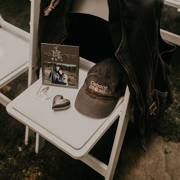 Ceremony chair memorializing bride's late grandfather with a photo, dog tags, a silver heart, Carhartt hat, and a Carhartt vest on the back of the chair