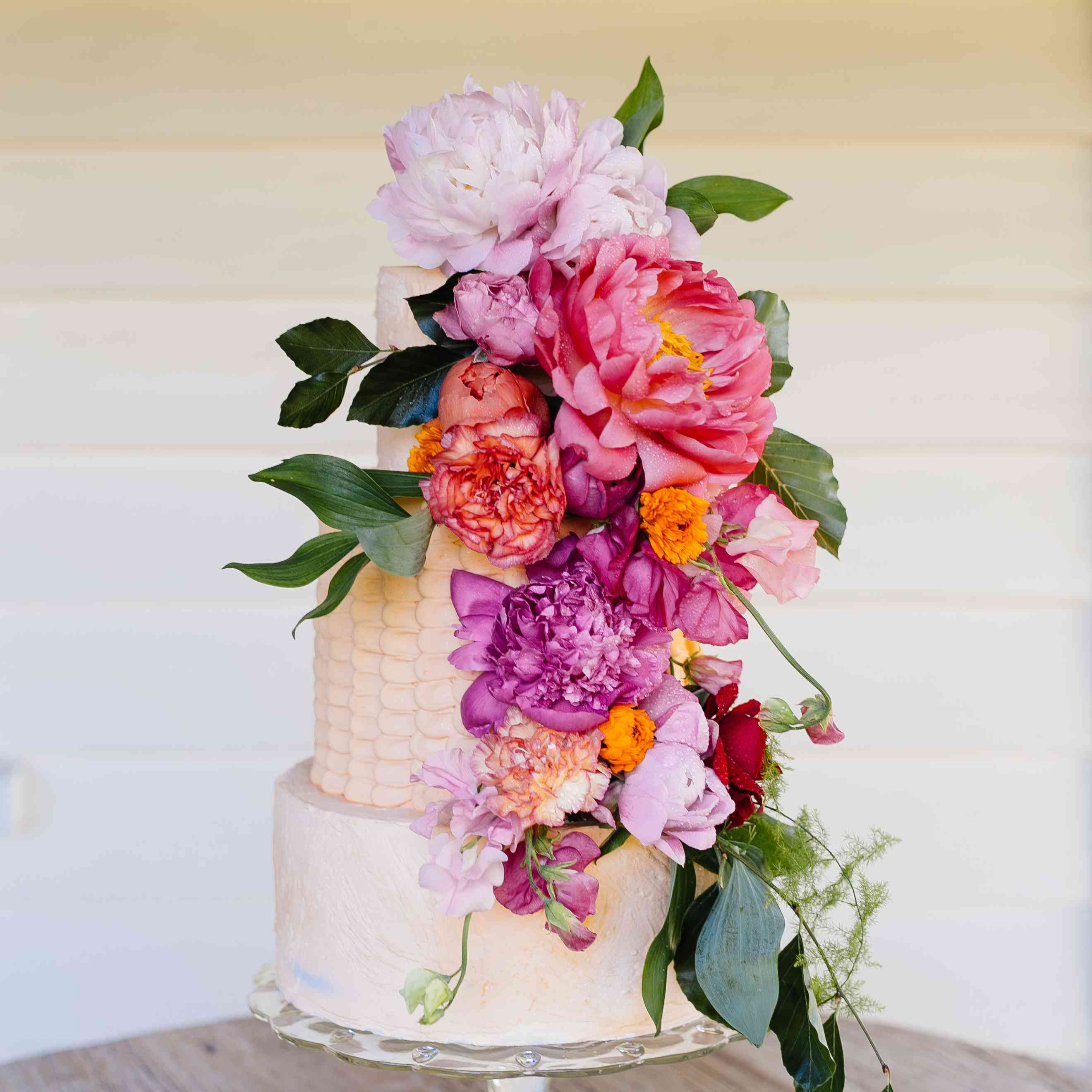 A wedding cake with cascading fresh florals