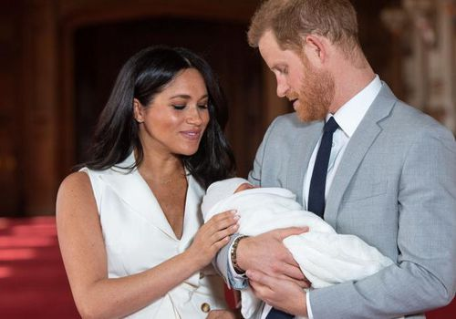 Meghan Markle and Prince Harry pose with their newborn son Archie Harrison Mountbatten-Windsor during a photocall in St George's Hall at Windsor Castle.