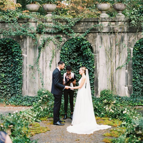 bride, groom, and officiant in garden setting