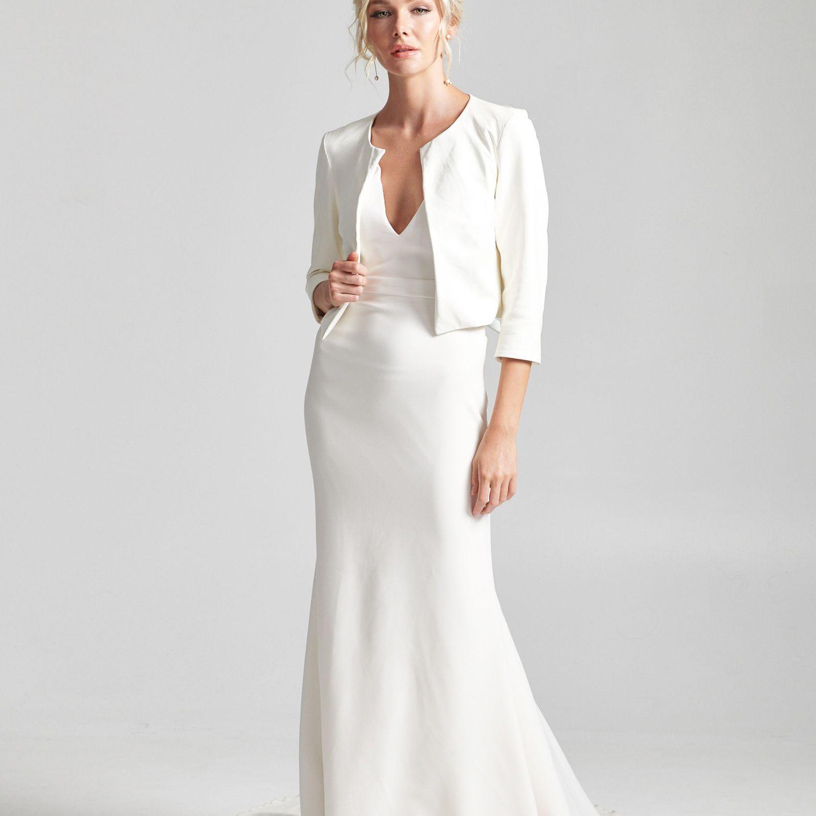 Model in V-neck wedding dress with white cropped jacket