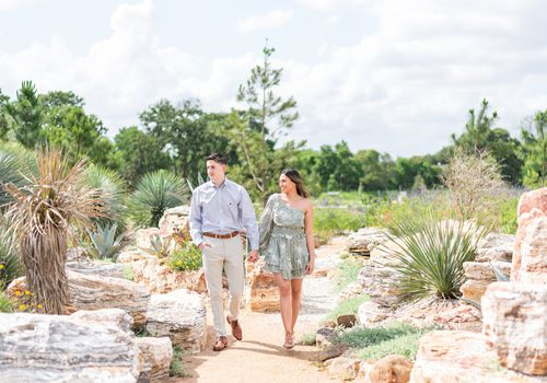A couple holding hands walking through the Houston Botanic Garden