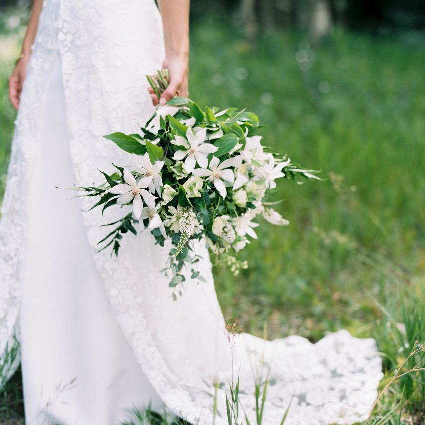 Bride holding all white bouquet of clematis, hellebores, lysimachia, and ferns