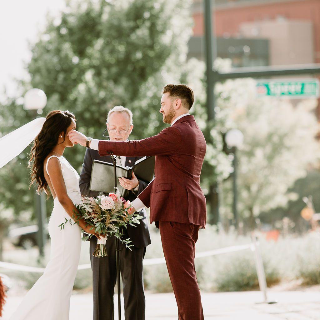 Groom reaching across during wedding ceremony to wipe bride's tears