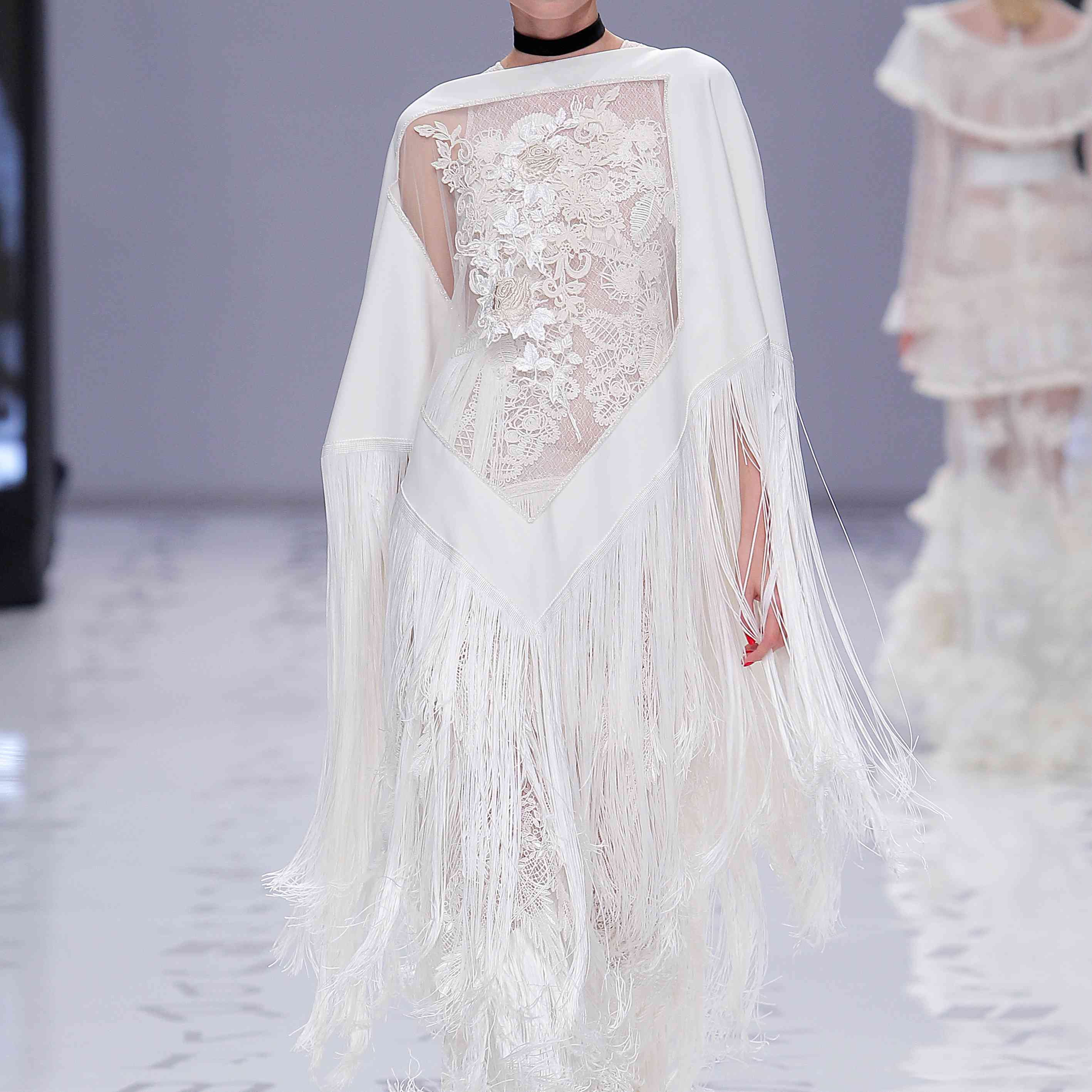 Model in a sleeveless floral lace dress and floral-embroidered beaded poncho with dramatic fringe detail.