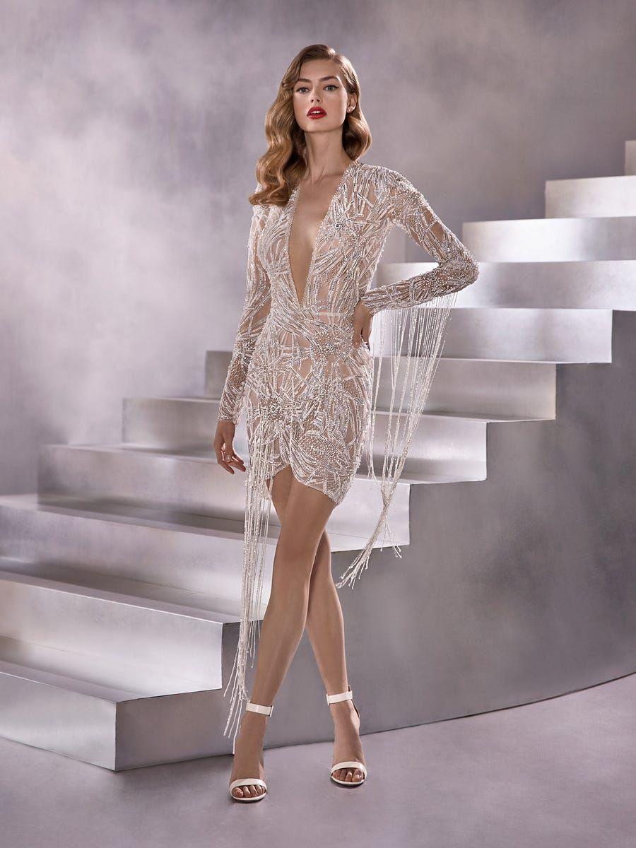 Model in sheer beaded short wedding gown with long sleeves