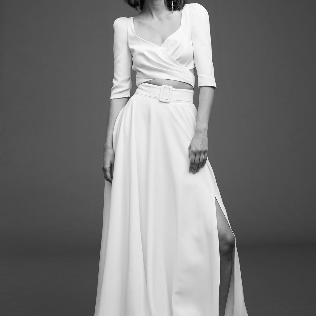 Model in three-quarter sleeve crop top with wide skirt with belt and side slit