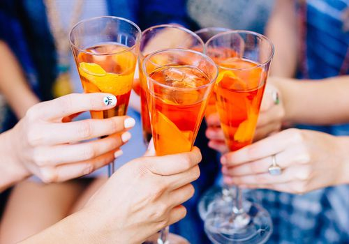 Women clinking cocktail glasses together.