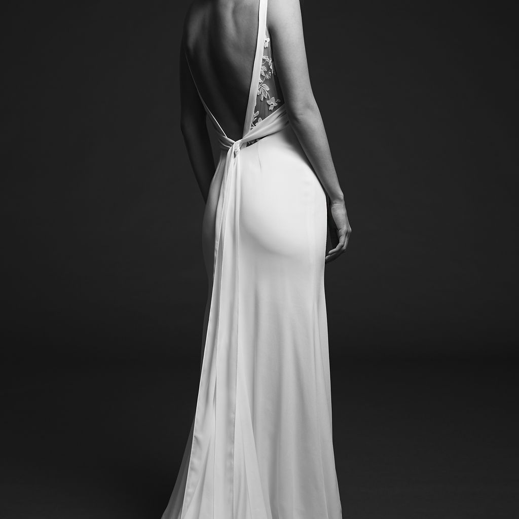 Model in wedding gown with open V back and train