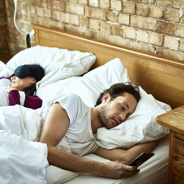 Couple not looking at each other in bed