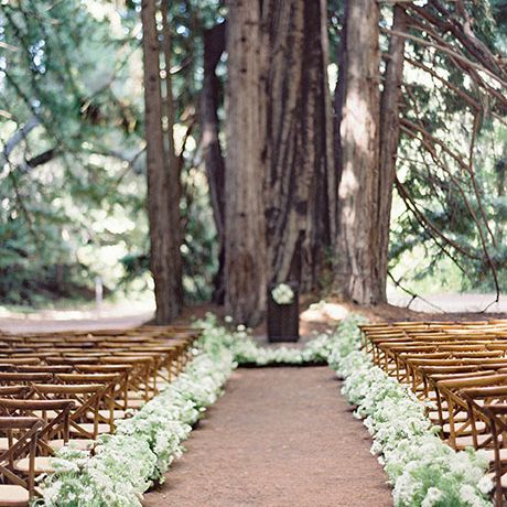 Wedding aisle in the woods lined with flower pots