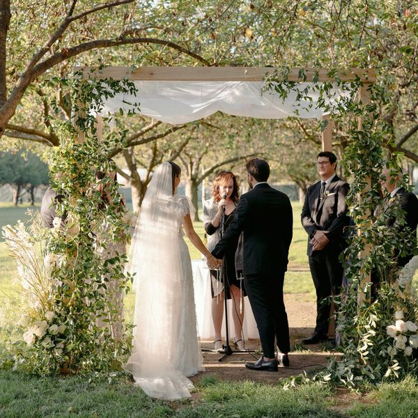 bride and groom under chuppah with greenery