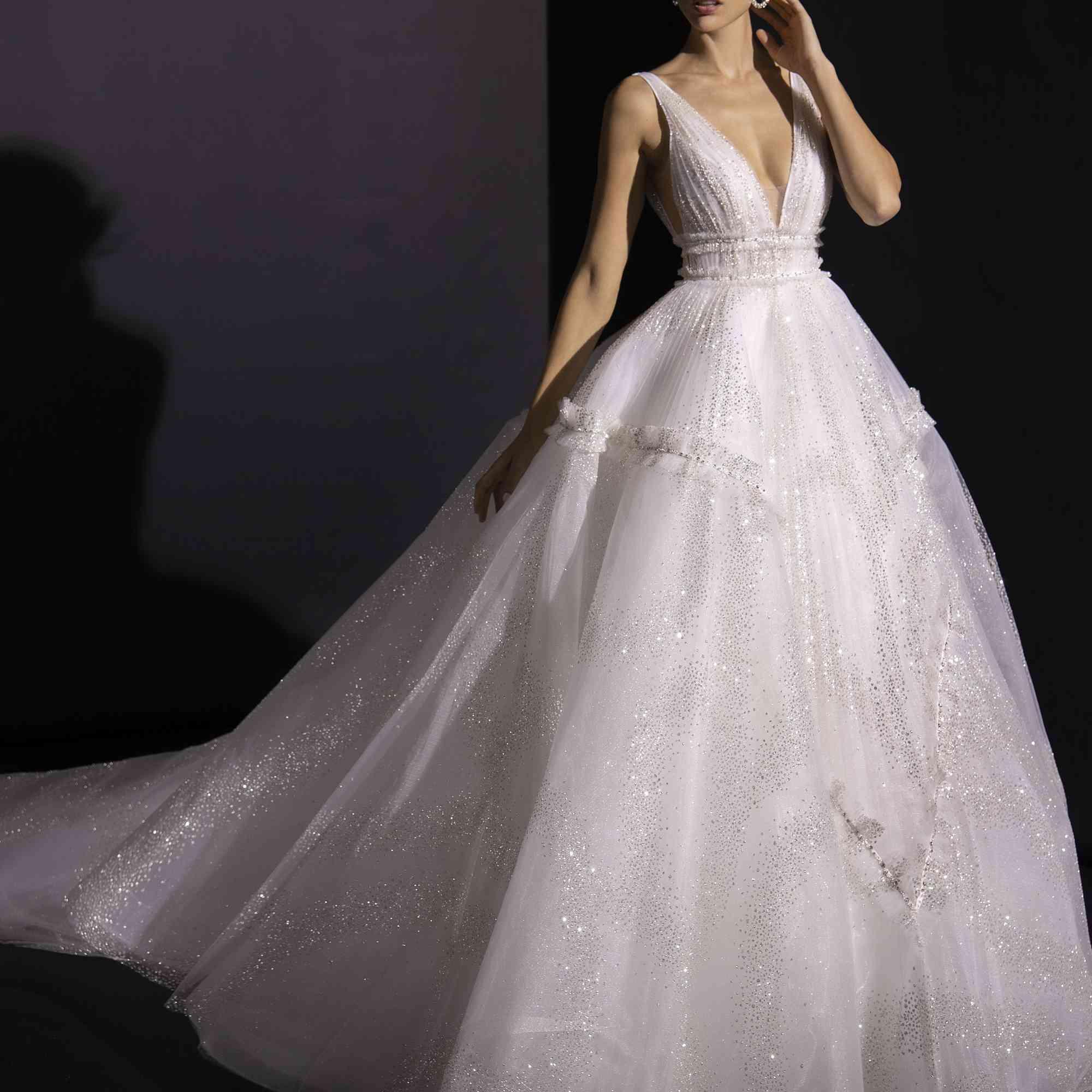 Model in voluminous glitter tulle ballgown with deep V neck