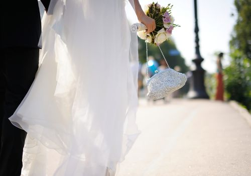Bride holding a purse walking with groom