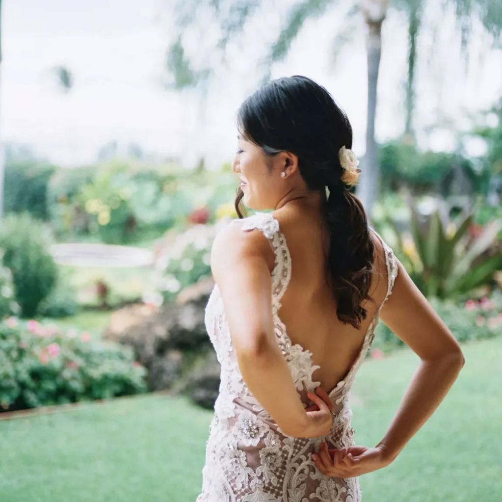 Bride with floral ponytail zipping up dress